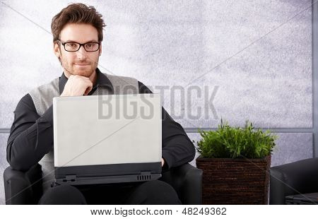 Confident businessman sitting in office lobby, working on laptop, smiling.