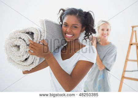 Housemates carrying rolled up rug and smiling at camera in new home