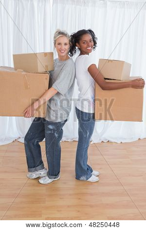 Smiling friends standing back to back holding moving boxes looking at camera