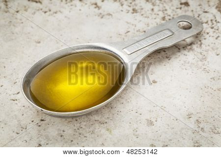Measuring tablespoon of olive oil on a kitchen counter (ceramic tile)