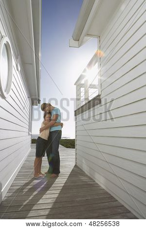 Side view of happy mother hugging daughter in passageway between beach houses