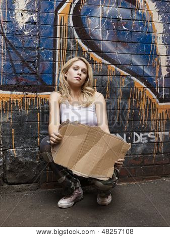 Portrait of a young woman squatting by brick wall pretending begging