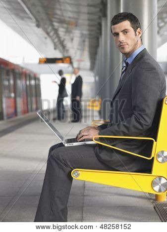 Side view of a young businessman using laptop at the train station