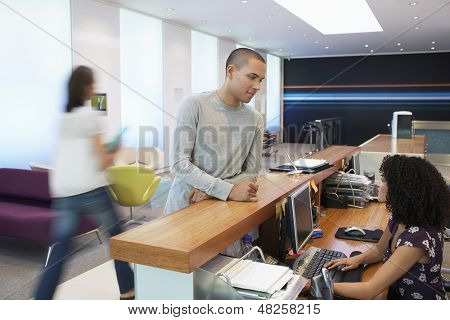 Man talking to receptionist at the reception desk in office