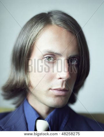 Closeup portrait of a serious man against colored background