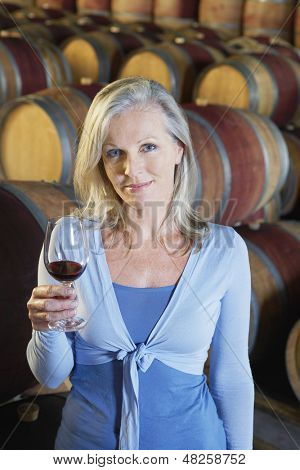 Portrait of beautiful middle aged woman holding glass of red wine in cellar