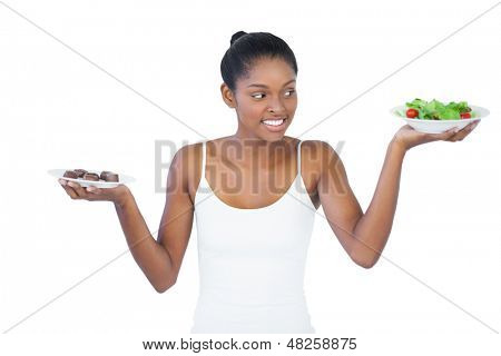 Cheerful woman deciding to eat healthily or not on white background