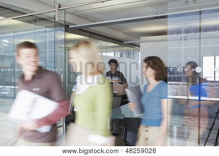 Multiethnic blurred office workers leaving conference room