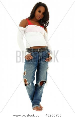 Beautiful black woman in torn jeans and white shirt standing on white floor. Clipping path.