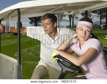 Young couple relaxing in golf cart