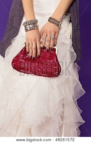 closeup of bride wearing ruffles dress and red luxury bag with fashion bangles and large diamond ring on purple studio background