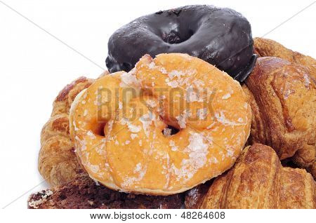 closeup of some different pastries, such as croissants and regular donuts and chocolate coated donuts, on a white background