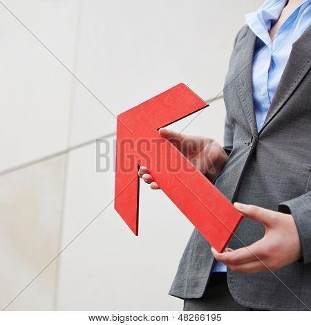 Flecha roja apuntando hacia arriba y se lleva a cabo por mujer