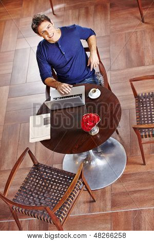 Young business man in caf���© working at laptop and drinking coffee