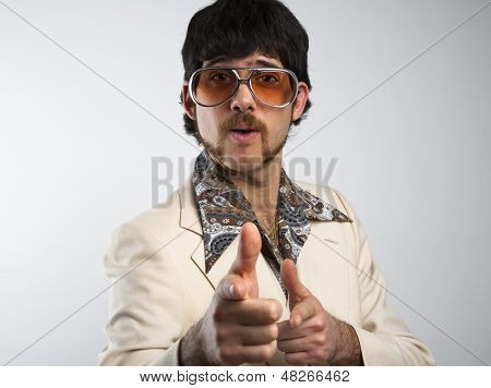 Portrait of a retro man in a 1970s leisure suit and sunglasses pointing to the camera