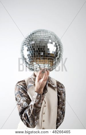Portrait of a retro man in a 1970s leisure suit holding a disco ball - mirror ball in front of his face