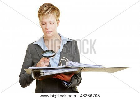 Business woman with big magnifying glass reading fineprint of a contract