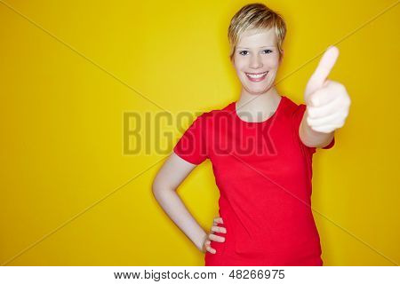 Young happy woman holding her thumbs up on yellow background
