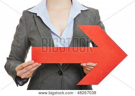 Manos de una mujer sosteniendo una gran flecha roja apuntando a la derecha