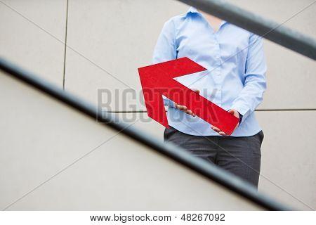 Mujer sosteniendo gran flecha roja apuntando hacia arriba