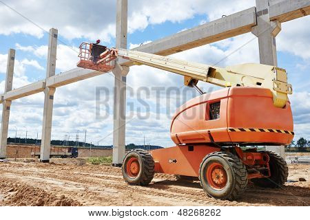 builder worker putting cement mortar on concrete pole joint at construction site using lifting boom machinery