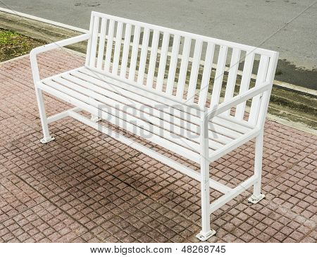 A single white bench in a park