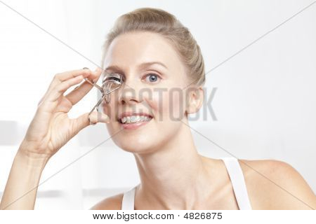 Caucasian Brunnete Curling Her Eyelashes With Curler
