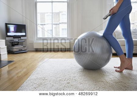 Low section of a young woman standing at fitness ball and watching television