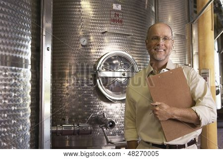 Portrait of middle aged winemaker with clipboard standing next to wine vats