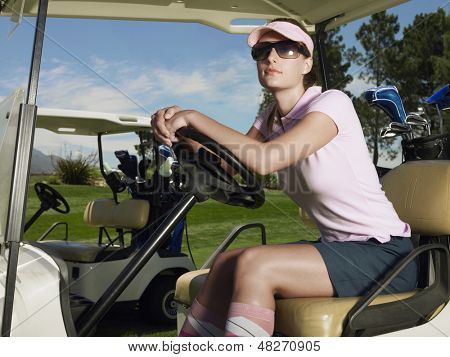Beautiful female golfer wearing sunglasses in golf cart