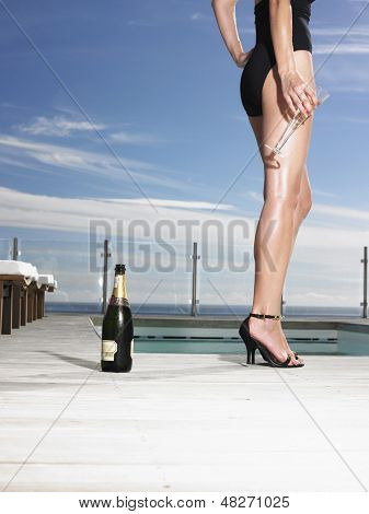 Lowsection of a young woman in bathing suit holding champagne glass at poolside