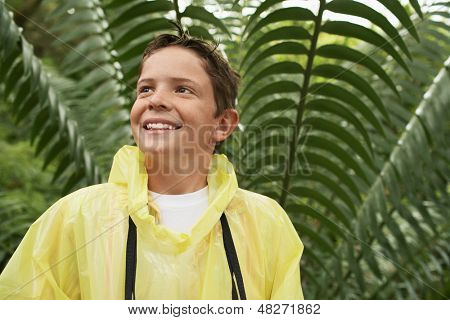 Happy young boy in raincoat standing in front of large fern during field trip