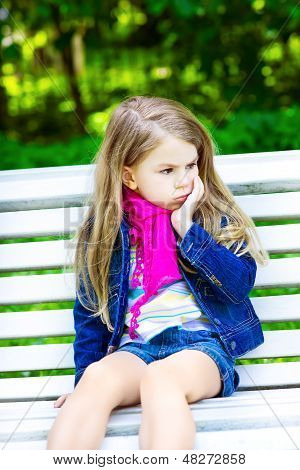 Sad Blond Little Girl Sitting On A Bench In The Park