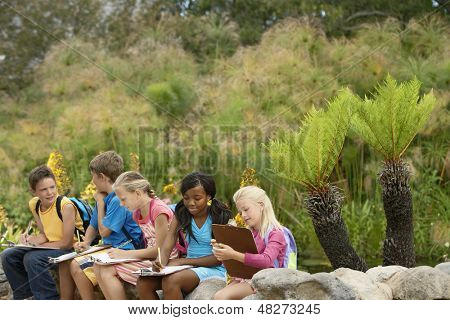 Young children preparing notes on clipboards during field trip