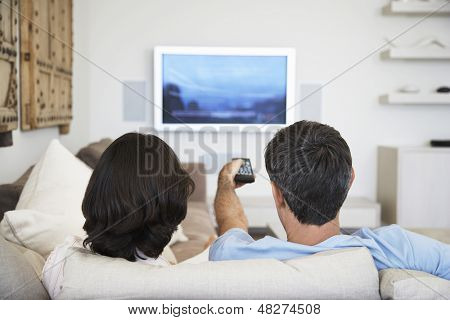 Rear view of couple watching television in living room