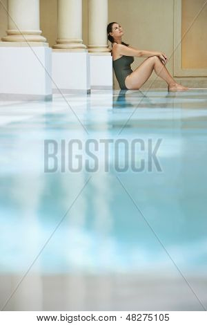 Side view of young woman sitting by swimming pool