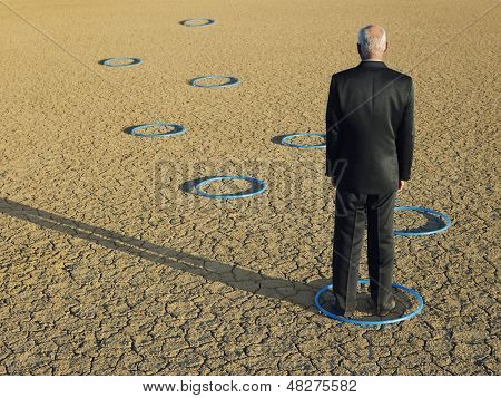 Rear view of middle aged businessman standing in ring at barren landscape