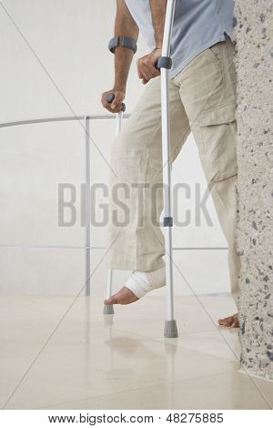 Low section of man with broken leg walking with crutches at home