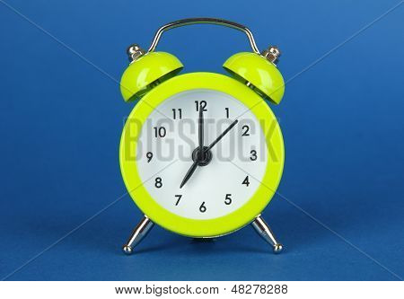 Green alarm clock on blue background