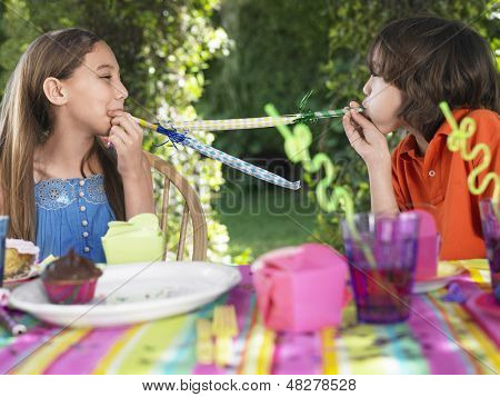 Young boy and girl blowing party puffers at each other in outdoor birthday party