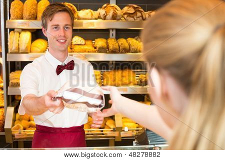 Shopkeeper In Bakery Giving Bag Withf Bread To Customer