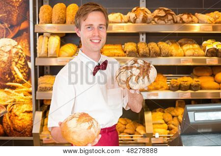 Salesman In Bakery Holding Different Types Of Bread