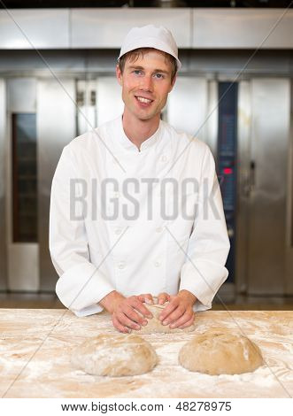 Smiling Baker Kneading Dough In Bakery