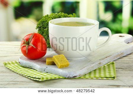 Cup of soup with bouillon cubes on wooden table