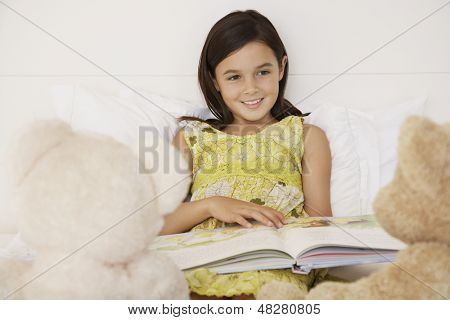 Happy girl reading story book to her teddy bears in bed