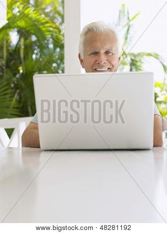 Smiling mature man using laptop at verandah table