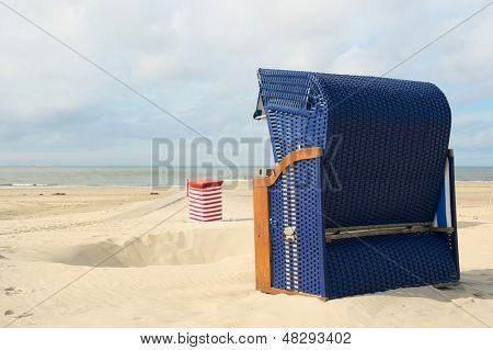 Beach of German wadden island with typical blue wicker chair