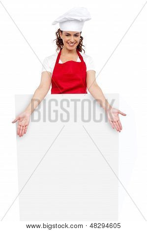 Female Chef Posing Behind Blank White Billboard