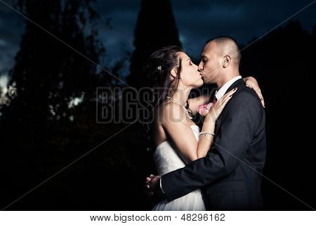 Portrait Of Young Married Couple Kissing Outdoors