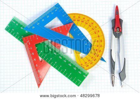 Conjunto de líneas multicoloras de triángulos, transportadores y pinza. Sobre un fondo blanco.